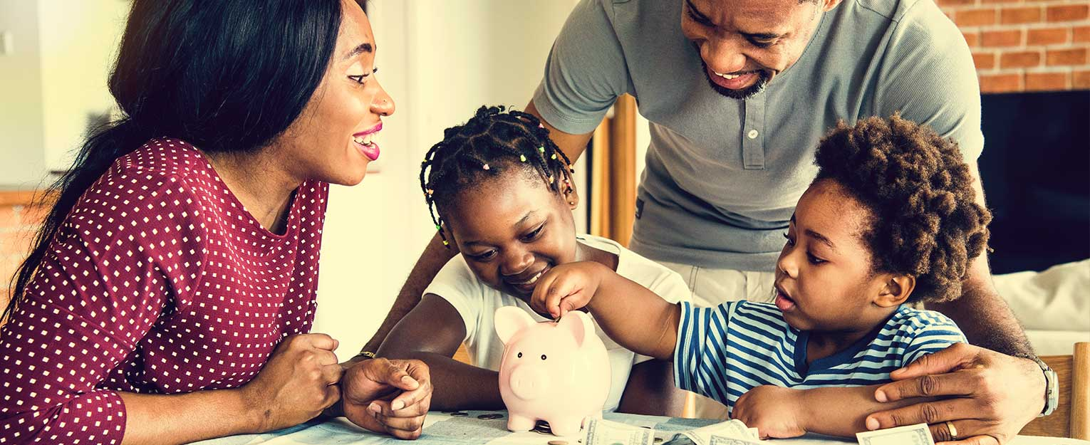 Young children saving money in a piggy bank with their parents.