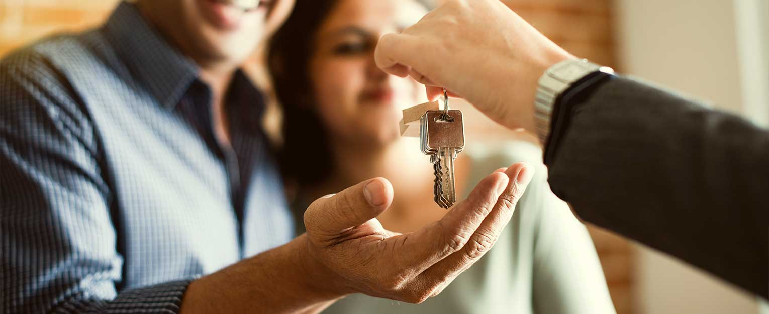 Loan officer handing over keys to new homeowners.