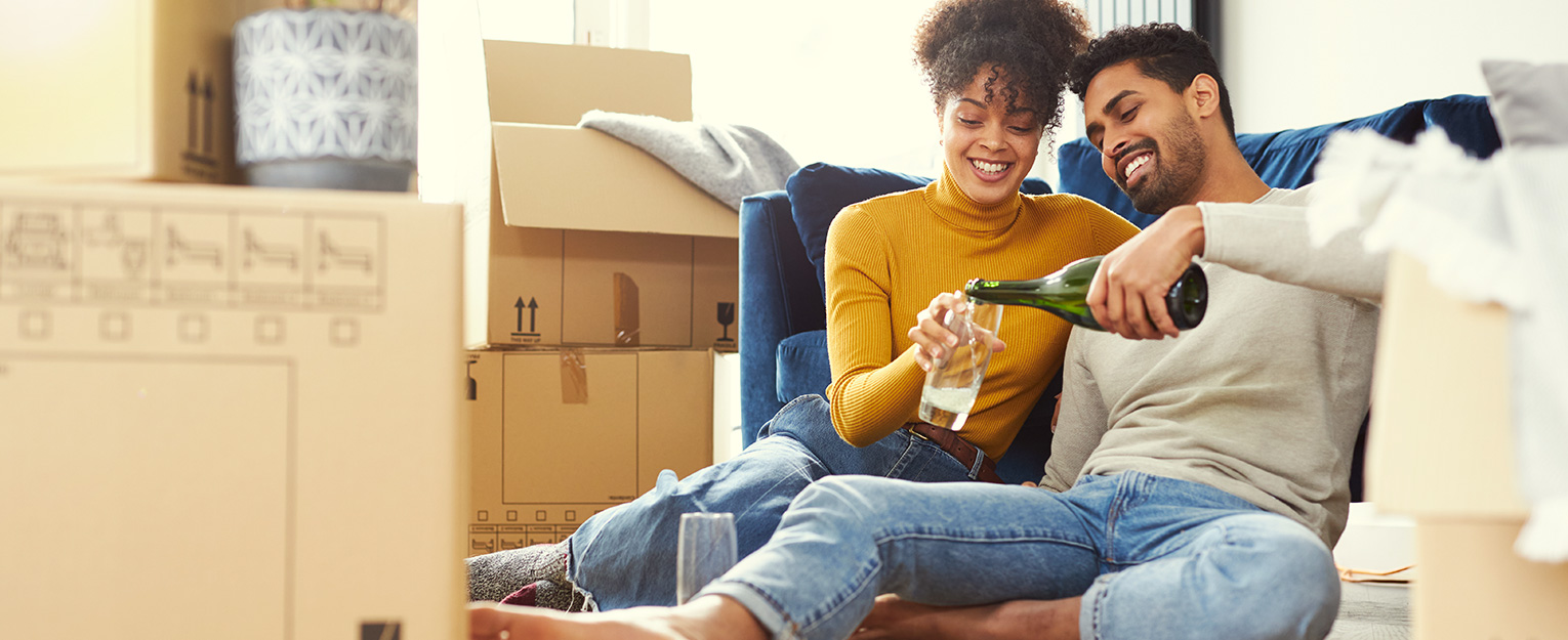 Couple pouring champagne and celebrating in new home.