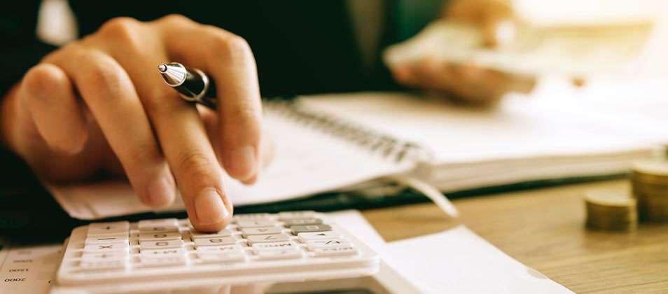 Closeup of hand using calculator.