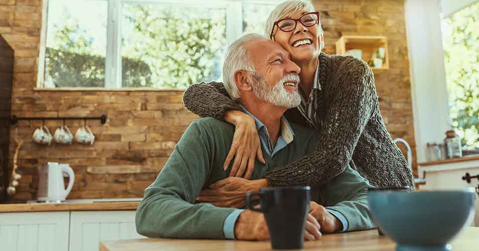 Older couple smiling and hugging.