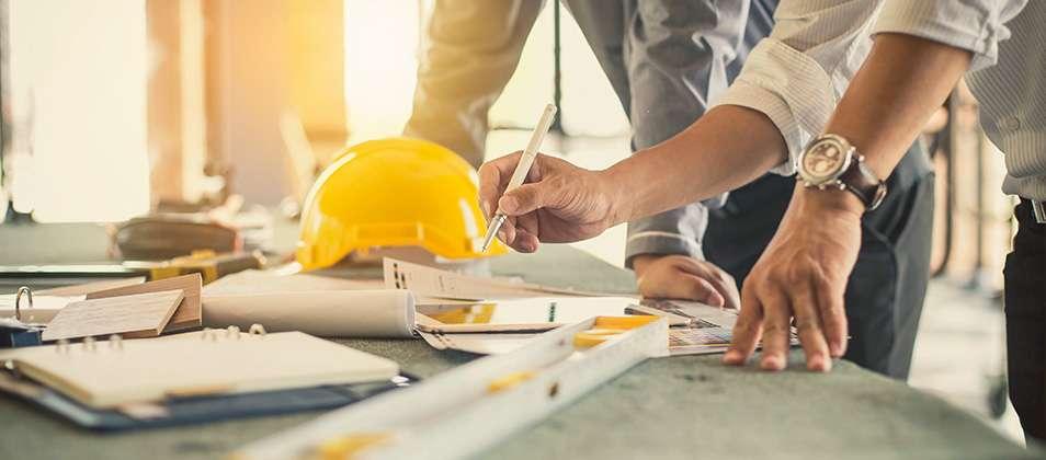 Construction contractors reviewing building plans.